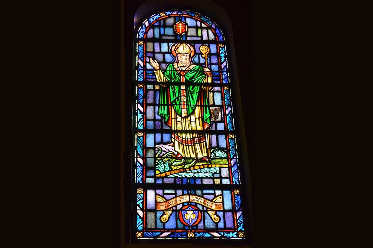 St. Patrick, bishop, is dressed in green vestments holding his staff. Born in Great Britain, he became a missionary to Ireland where they have taken him as their patron saint. His feast day is March 17.