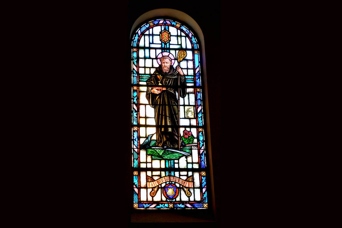 "St. Benedict is dressed in traditional brown robes of a monk, holding a closed book and a chalice with a snake. He was a great innovator setting up the first communities of followers, the Order of St. Benedict, and giving them ""The Rule"" to live by. This Rule consisted of primarily prayer, known as the Office, and reading the Bible using Lectio Divina. His feast day is July 11. He is the patron saint of Europe and the St. Benedict medal carries with it many protections."